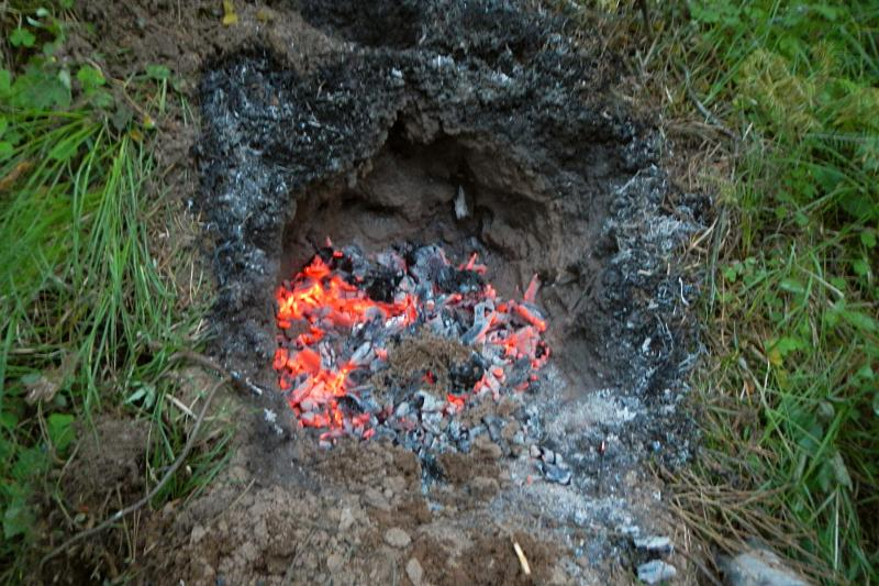 Земляная печь для запекания курицы и красные угли в ней