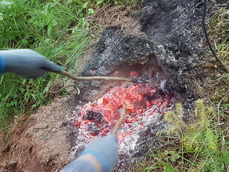 Разгребаем пышущие жаром угли в земляной печи для запекания курицы в фольге