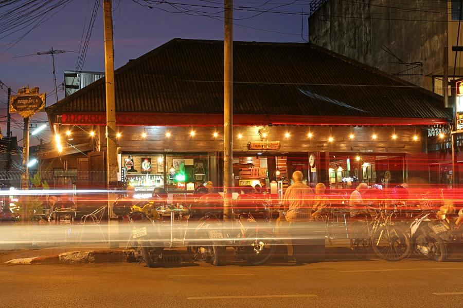 Ночной Чиангмай: вечерний придорожный бар, мотоциклы и размазанные огни от фар проезжающих машин