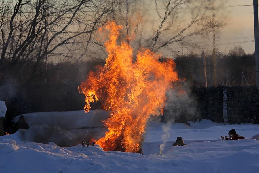 Масленица: сжигание чучела зимы. Яркие оранжевые всполохи огня, языки пламени. Юркин парк, 10 марта 2019 г.