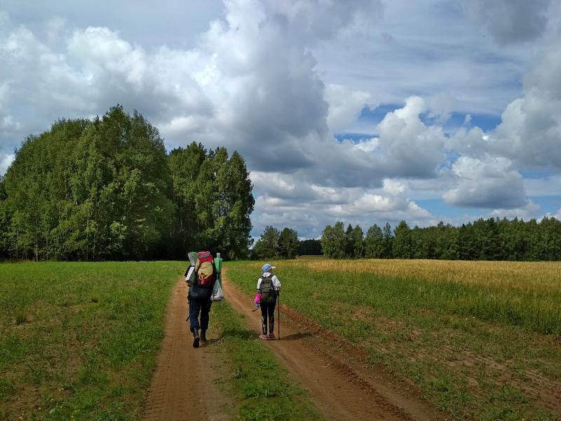 Полевая дорога, туристы и облака на небе